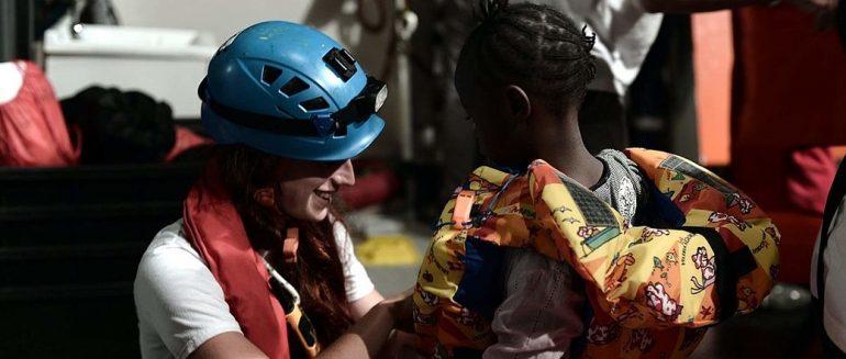 Una voluntaria ayudando a una niña a ponerse el chaleco salvavidas en el Aquarius