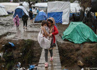 Niña con un bebé en brazos andando por un campo de refugiados en Grecia