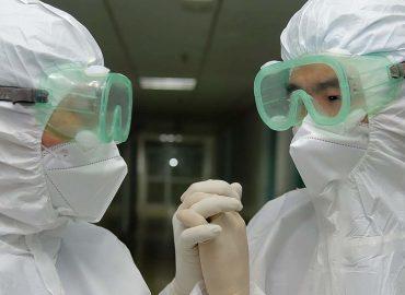 Dos sanitarios con protección se dan la mano de forma amigable