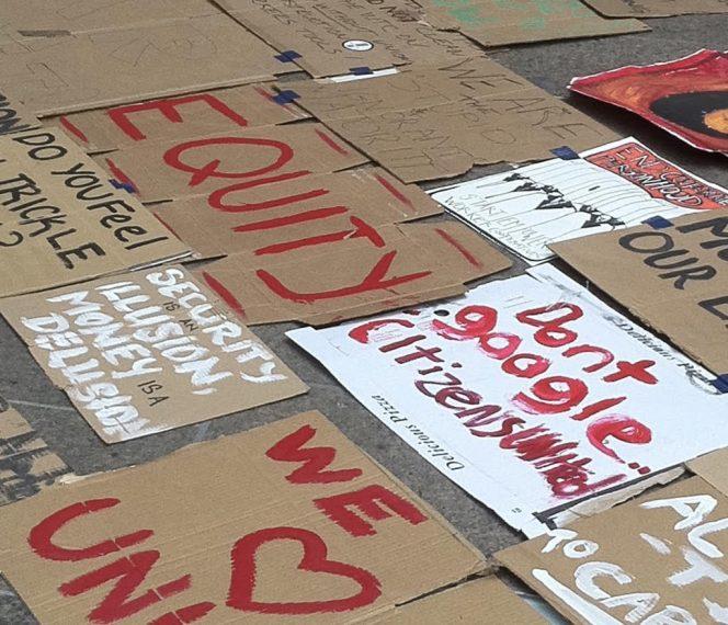 Pancartas de cartón con lemas sobre equidad, unidad y solidaridad