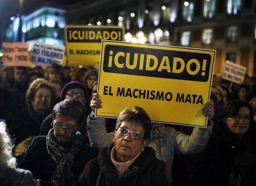 """Una manifestación en el que se ve a una mujer mayor con cara triste y detrás una pancarta que reza """"Cuidado, el machismo mata"""""""