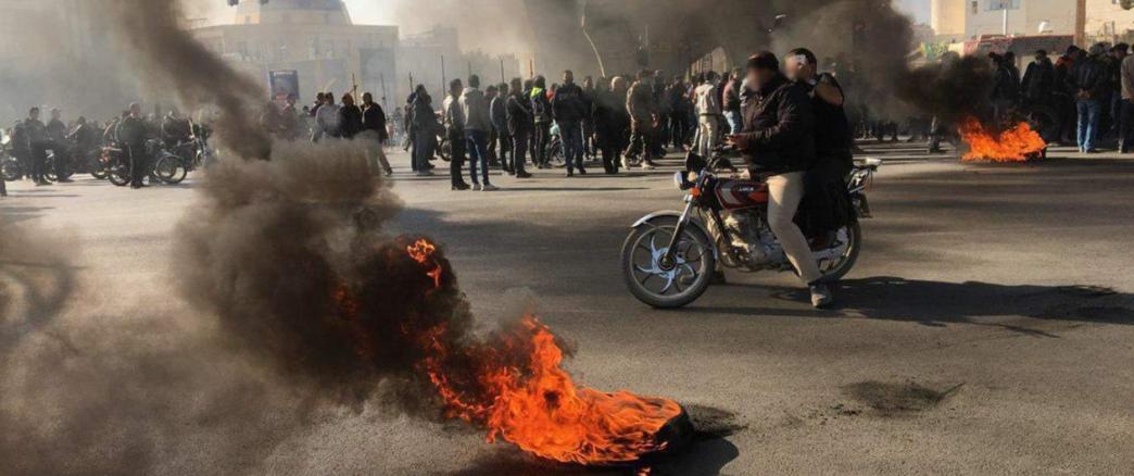 Dos chicos en una moto en medio de un ambiente de revueltas en el que se ve una muchedumbre y dos fuegos prendidos