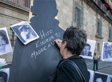 """Una mujer mejicana está escribiendo en un cartel situado en la calle: """"Hijo, escucha, tu madre está..."""""""