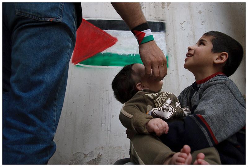 La mano de un hombre, con una bandera palestina en su muñeca, acaricia un bebé sujetado por un niño. En el fondo, a un metro, un pared con la bandera palestina pintada con spray.