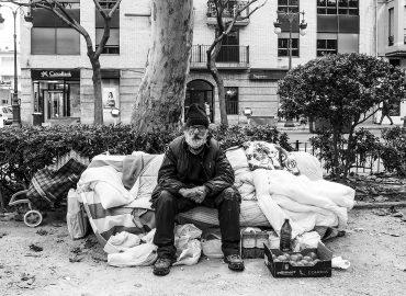 Un hombre indigente sentado en la calle en un sillón de bolsas llenas de enseres