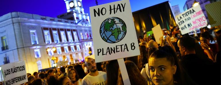 Una joven sostiene una pancarta que reza No hay planeta B en una manifestación en la Puerta del Sol
