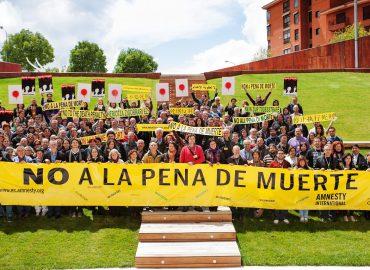 Un numeroso grupo de activistas de Amnistía Internacional portan una pancarta que reza 'no a la pena de muerte'