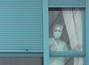 Una sanitaria con mascarilla mira desde una ventana de un centro sanitario con las manos apoyadas en el cristal de la ventana
