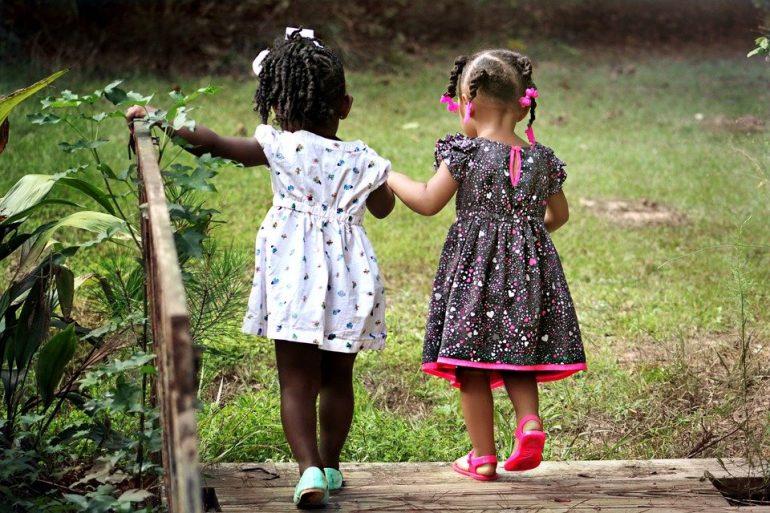 Dos niñas pequeñas andando juntas de la mano