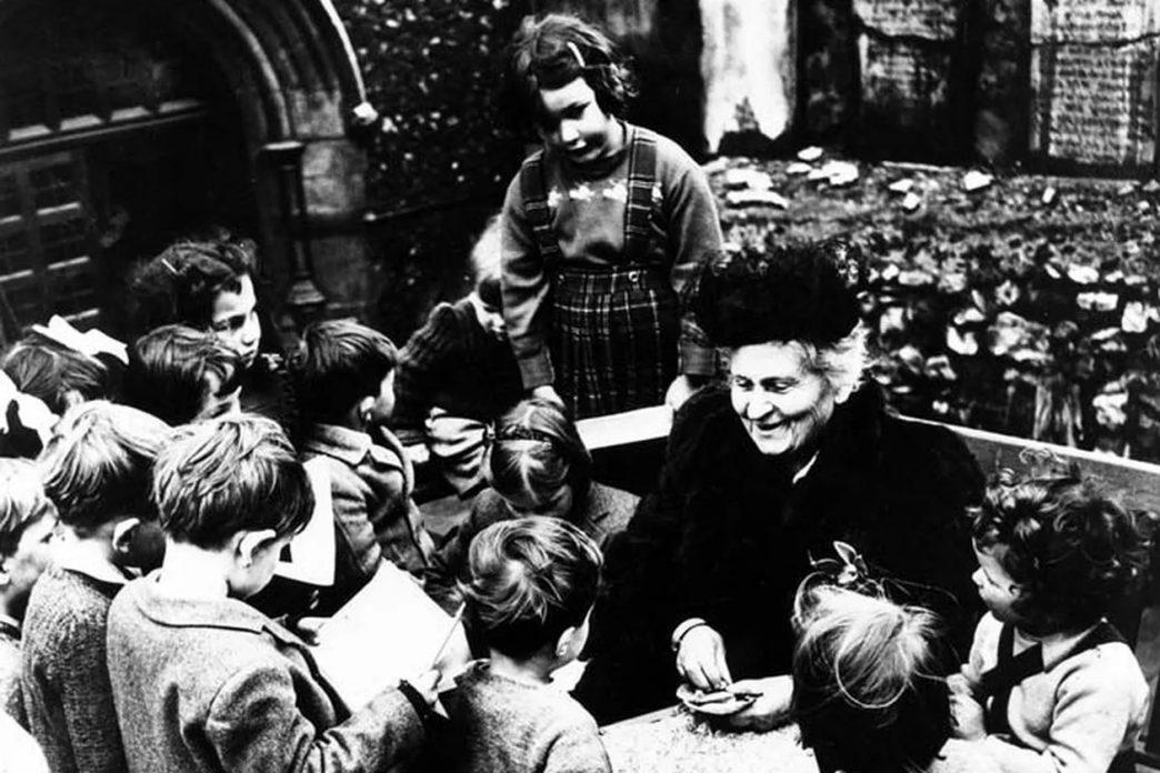 María Montessori rodeada de niños en un espacio ajardinado.