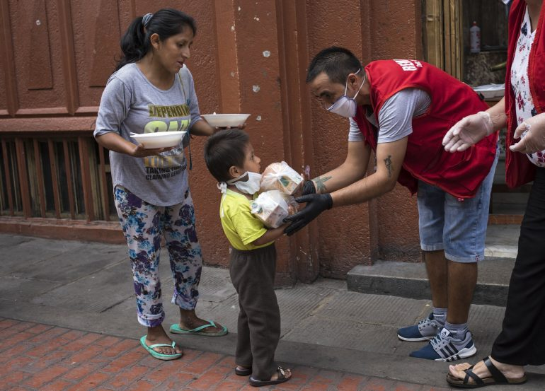 Maria Isabel Nieto and her son Jesus Anderson receive their lunch, provided to the homeless by a charity organization in Lima, Peru, Thursday, March 26, 2020, on the second week of a government decreed state of emergency that restricts residents to their homes to help contain the spread of the new coronavirus. COVID-19 causes mild or moderate symptoms for most people, but for some, especially older adults and people with existing health problems, it can cause more severe illness or death. © AP Photo/Rodrigo Abd